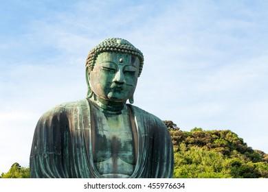 Medium shot from side of big bronze Buddha in Kamakura, Japan, on a blue sky.