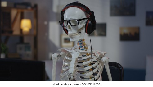 Medium shot of a skeleton wearing headphone dancing while sitting at a computer