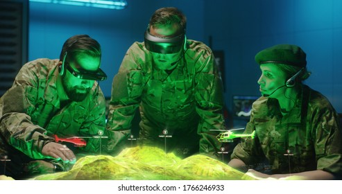 Medium shot of soldiers discussing military strategy with holographic landscape display