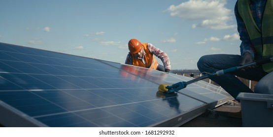Medium shot of technicians cleaning and maintaining solar panels
