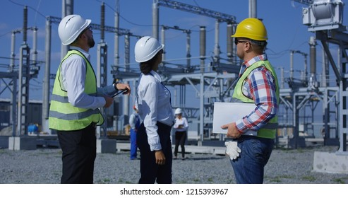 Medium shot of three electrical workers reviewing documents on a tablet during an inspection against the background of a transformer station