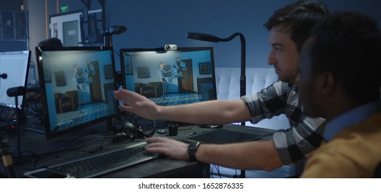 Medium shot of two digital artists discussing about the details of an animated film