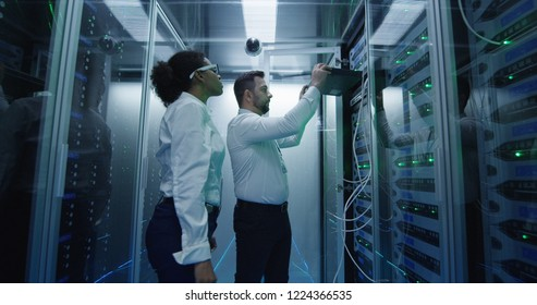 Medium shot of two diverse employees working in a data center server room taking networking equipment out for repair and maintenance