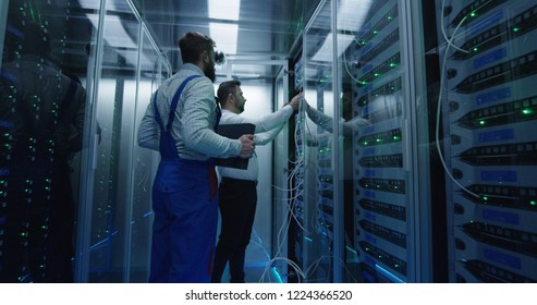 Medium shot of two men working in a data center taking networking equipment out for repair and maintenance