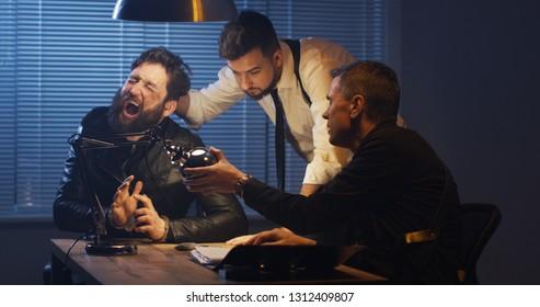 Medium shot of two policemen using force while interrogating a drug dealer