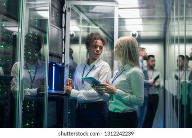Medium shot of two women working in a data center with rows of server racks and checking the equipment and discussing their work