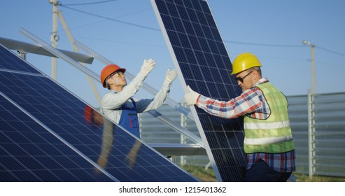 Medium shot of two workers in safety vests and hardhats installing photovoltaic panels on a metal basis at a solar farm