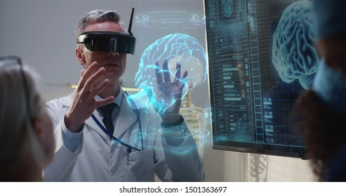 Medium shot of a VR headset wearing doctor explaining to his colleagues while moving holographic 3d brain image
