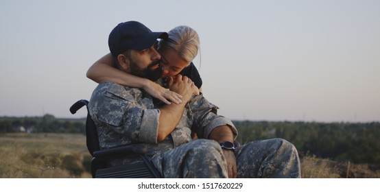 Medium shot of wife hugging wheelchaired soldier husband