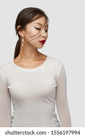 Medium shot of a young Asian woman in an ivory white blouse and with a stud earring made as a string of golden wire balls and nacre gem pellets.