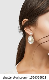 Medium shot of a young Asian woman in an ivory white blouse and with a stud earring made as a shimmering pearl with dangling nacre seashells.