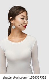 Medium shot of a young Asian woman in an ivory white blouse and with a golden hook earring with dangling nacre disc.