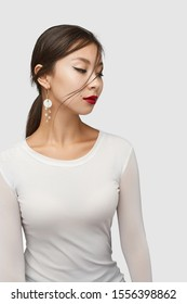 Medium shot of a young Asian woman in an ivory white blouse and with a hoop earring made as a golden ring with white nacre discs and a golden twig with crystal beads.