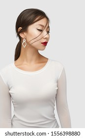Medium shot of a young Asian woman in an ivory white blouse and with a stud earring made as a golden semi-sphere with nacre gem ring and pearl rhombus.
