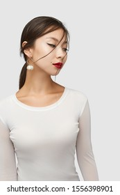 Medium shot of a young Asian woman in an ivory white blouse and with a stud earring with a golden rhombus frame with dangling nacre seashells.
