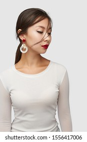 Medium shot of a young Asian woman in an ivory white blouse and with a stud earring made as a red gem heart-shaped base with dangling wavy golden disk and a white nacre holed circle.