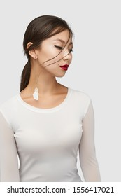 Medium shot of a young Asian woman in an ivory white blouse and with a stud earring with long golden chains with dangling white fabric feather and nacre disc.
