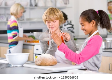 A medium shot of a young blonde boy and an African American girl sprinkling flour on a bread in a economics class.