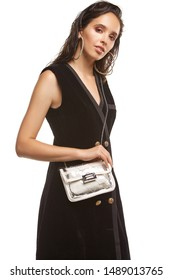 Medium shot of a young chestnut European lady in a brown buttoned dress with a light crossbody bag. The transparent bag with leather garniture, silver fastener and a white inlying make-up bag