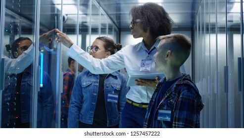 Medium shot of a young female technician showing around children in a server park
