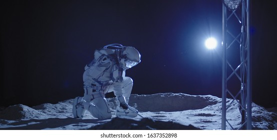 Medium shot of a young male astronaut kneeling on the Moon surface