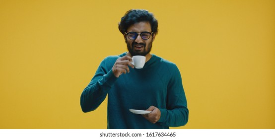 Medium shot of young man drinking bad coffee