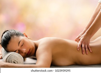Medium side view portrait of young woman having hot aromatic oil massage is spa.Therapist applying pressure on spinal column.