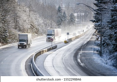 Medium size and Power capability day cab rig semi Truck for local deliveries with roof spoiler and dry van semi trailer running on the winter snowy and icy slippery road with divided concrete barrier
