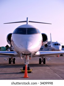 Medium sized jet planes sit on the tarmac at a small airport