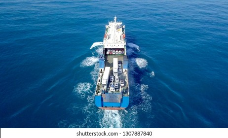 Medium sized Ro-Ro (Roll on/off) ship roaring across The Mediterranean Sea with cars and trucks seen on the upper deck - Aerial image.