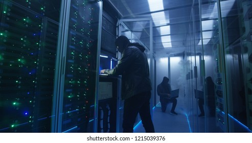Medium, slow motion shot of a two hackers finishing hack and escaping a spark and smoke-filled corporate data center