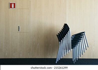 Medium stack of chairs in conference room beside fire extinguisher sign on wall