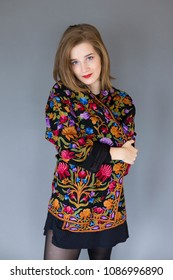 Medium vertical photo of stunning blue eyed girl in black miniskirt wrapping herself in warm multicoloured ethnic style jacket with floral pattern