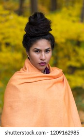 Medium vertical portrait of sultry hispanic young woman with hair up in a high bun draped in an orange shawl in front of soft focus Fall foliage