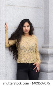 Medium vertical portrait of sultry hispanic young woman with long curly dark hair wearing elegant gold lace top and tight black jeans leaning against stone column