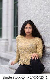 Medium vertical portrait of sultry hispanic young woman with long curly dark hair wearing elegant gold lace top and tight black jeans sitting at the base of a stone column with building in soft focus
