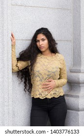 Medium vertical portrait of sultry hispanic young woman with long curly dark hair wearing elegant gold lace top and tight black jeans leaning against stone column while hugging herself