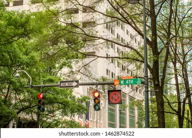 Medium view of office buildings through trees and looking slightly upward showing traffic poles, traffic lights, traffic signage and traffic surveillance camera in uptown Charlotte on Tryon street.