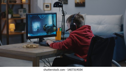 A medium wide shot of a disable young gamer playing video games online while sitting on his wheelchair