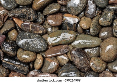 Medium-size pebble stone or river stone shot from above or top view as background in low vibrance tone.