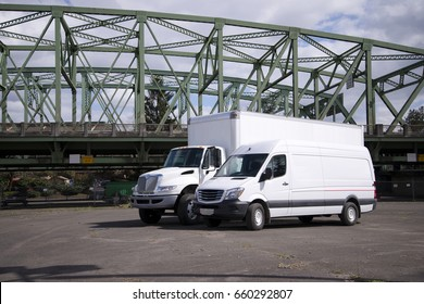 A medium-sized semi truck with a box trailer and a mini van for local freight or business use stand in anticipation of goods and orders for delivery to the public addresses or commercial enterprises