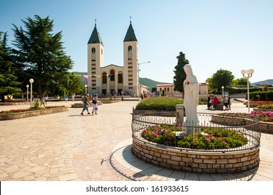 MEDJUGORJE, BOSNA AND HERZEGOVINA - JULY 28: Pilgrims visit the church and nearby Apparition Hill in Medjugorje, Bosnia and Herzegovina on July 28,2012. In the foreground is the virgin Mary statue.