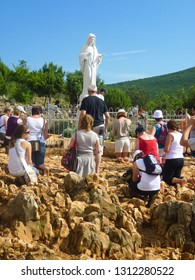 Medjugorje / Bosnia and Herzegovina - 07 31 2011: crowd of people kneeling and praying in front of white saint Mary statue in famous pilgrimage place Medugorje, Balkan, Southeastern Europe