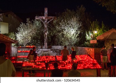 MEDJUGORJE, BOSNIA AND HERZEGOVINA, August 20 2016. Pilgrims coming to light a candle in front of the cross near the Saint James church.