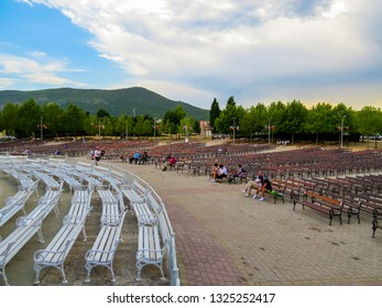 MEDJUGORJE, BOSNIA AND HERZEGOVINA - AUGUST 7, 2015: Unidentified people on the benches in front of the Church of Medjugorje.