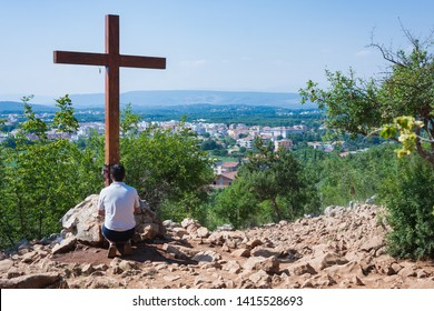 Medjugorje, Bosnia and Herzegovina - July 6 2012: A pilgrim kneeling and praying in front of wooden cross in famous pilgrimage place Apparition hill, Bosnia and Herzegovina.