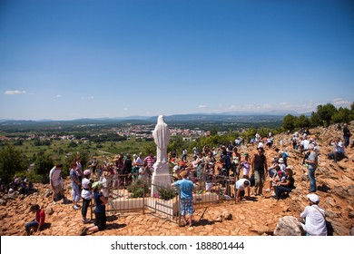 MEDJUGORJE, BOSNIA AND HERZEGOVINA - June 25, 2011: Unidentified pilgrims praying in front of Statue of Virgin Mary.