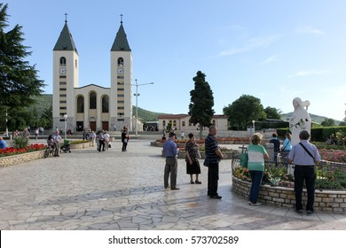 MEDJUGORJE, BOSNIA AND HERZEGOVINA, June 4 2016. Saint James church and unidentified pilgrims praying in front of the statue of Holy Mary - Our Lady of Medjugorje.