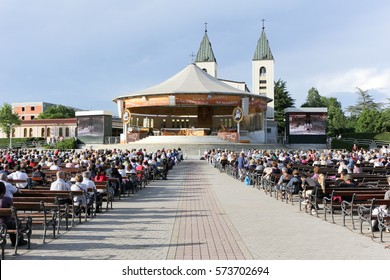 MEDJUGORJE, BOSNIA AND HERZEGOVINA, June 4 2016. Pilgrims praying in pews before the holy mass in the outdoor shrine behind Saint James church.