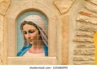 Medjugorje, Bosnia and Herzegovina - November 3, 2018: sunlight is enlightening painting of the Blessed Virgin Mary on tiles